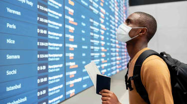 A man in a mask looks at airline destinations
