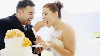 A couple feeding each other wedding cake on their wedding day