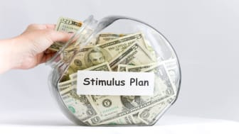 """picture of person taking money out of a jar labeled """"Stimulus Plan"""""""