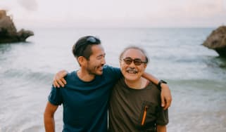 A father and his adult son smile on a beach.