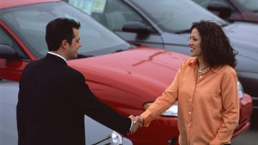 Man and woman shaking hands in a car lot