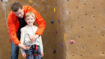 family of father and son ready for rock climbing in indoor gym