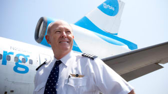 Capt. Dyson stands in front of an Orbis jet in his pilot's uniform.