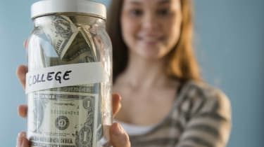 Photo of woman holding a jar of money for college