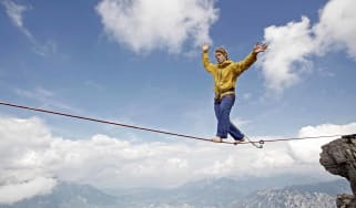 A man walks a tightrope in the mountains