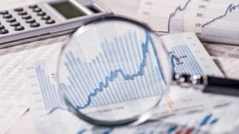 picture of magnifying glass over stock charts