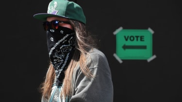 Photo of masked voter at poll