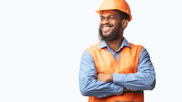 A man in a hardhat smiles.
