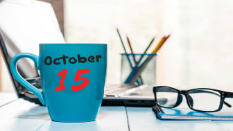 """picture of desk with """"October 15"""" written on a coffee mug"""