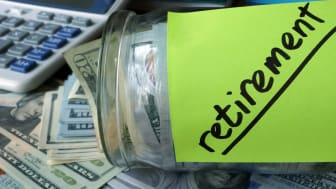 Jar with label Retirement Plan and money on the table. Saving money concept.