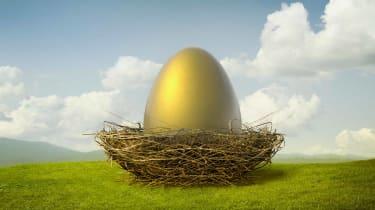 A huge golden egg sits in a bird's nest on a green hill under a blue sky.