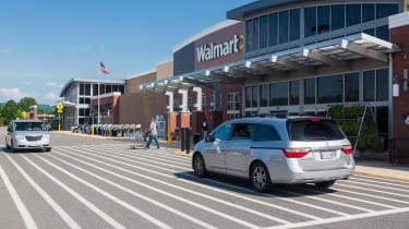 Cars pass in front of a Walmart entrance