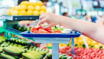 A hand takes a free food sample inside a supermarket