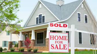 """picture of a house with a """"sold"""" sign in the front yard"""