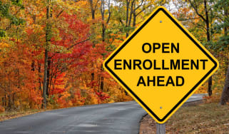 A sign by a road says open enrollment ahead.