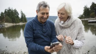 Senior couple using cell phone at lake