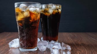 Two glasses filled with ice and cola sit on a tabletop next to ice