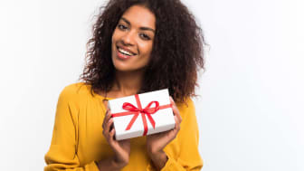 A woman holds a wrapped gift.