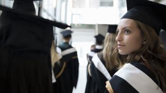Serious, confident female college student graduate in cap and gown
