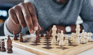 A man moves a piece on a chess board.