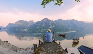 A person sitting alone on the edge of a pier looking at a beautiful mountain scene