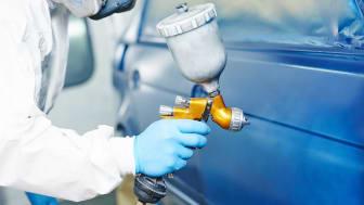 A worker sprays paint onto a car