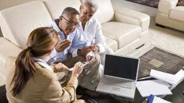 Senior African American couple meeting with female financial adviser reviewing report