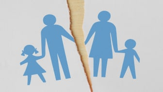 picture of a cut-out family on paper that is torn in half