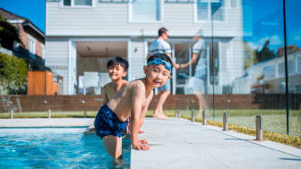 A family with young kids plays at a pool.