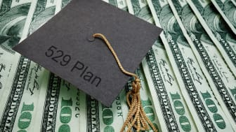 """picture of a graduation cap with """"529 plan"""" written on it sitting on one-hundred dollar bills"""