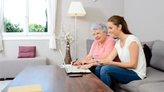 A grandmother looking at a computer with her daughter