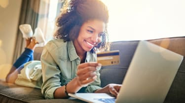 Shot of a cheerful young woman doing online shopping while lying on a couch at home during the day