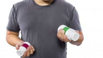 Male comparing bottles of medicine or dietary supplements.He is holding two pill bottles for comparison.The bottles have copyspace for logos.The image can also be depicting a comparison betwe