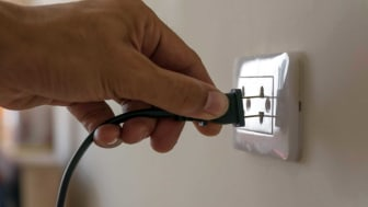 A man plugging a cord into a wall socket