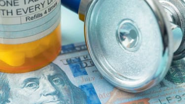 Pill bottle and stethoscope laying on $100 bill