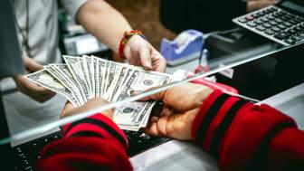 A teller handing a customer several bills in numerous denominations