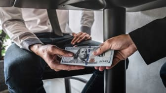 picture on money being given under a table
