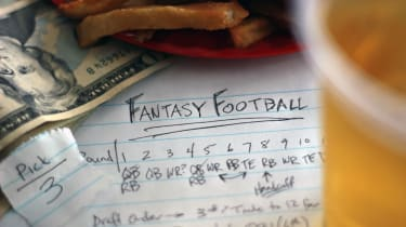 Group of fantasy football draft elements which includes draft paper, pick, money, food and beer.
