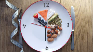 A plate with numbers on it like a clock and healthy foods.