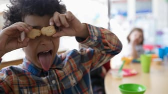 A child holds animal crackers on his eyes