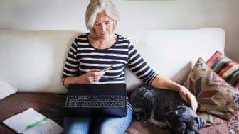 Senior woman using credit card and laptop while stroking dog on sofa