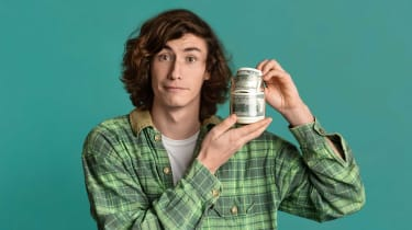 A teenager holds a jar full of $100 bills.