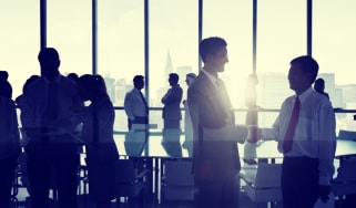 Business people shaking hands in an office building against a New York skyline.There is a large desk in the center of the room surrounded by office chairs.