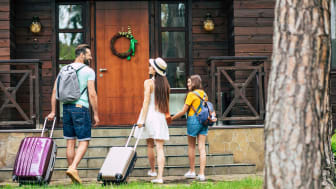 A family walks up to a vacation house.