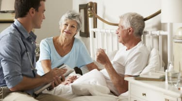 Doctor On Home Visit Discussing Health Of Senior Male Patient With Wife In Bedroom.