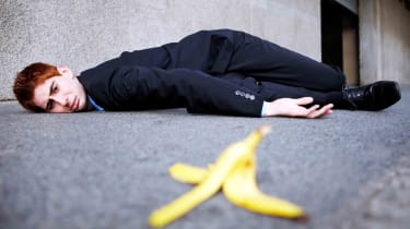 A businessman is on the ground after slipping on a banana peel.