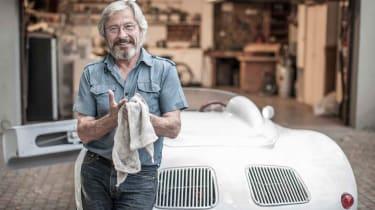 A wealthy man works on his sportscar.