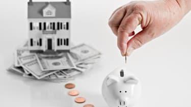 A hand putting money into a piggy bank