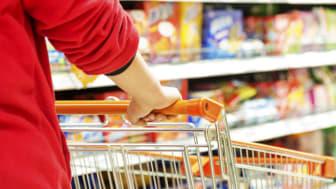 A shopper pushes a grocery cart down a supermarket aisle