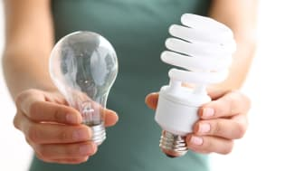 Hands holding traditional and energy efficent lightbulbs